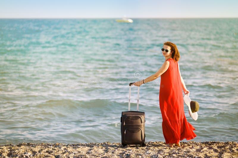Femme dans la robe rouge avec la mer de valise photo stock