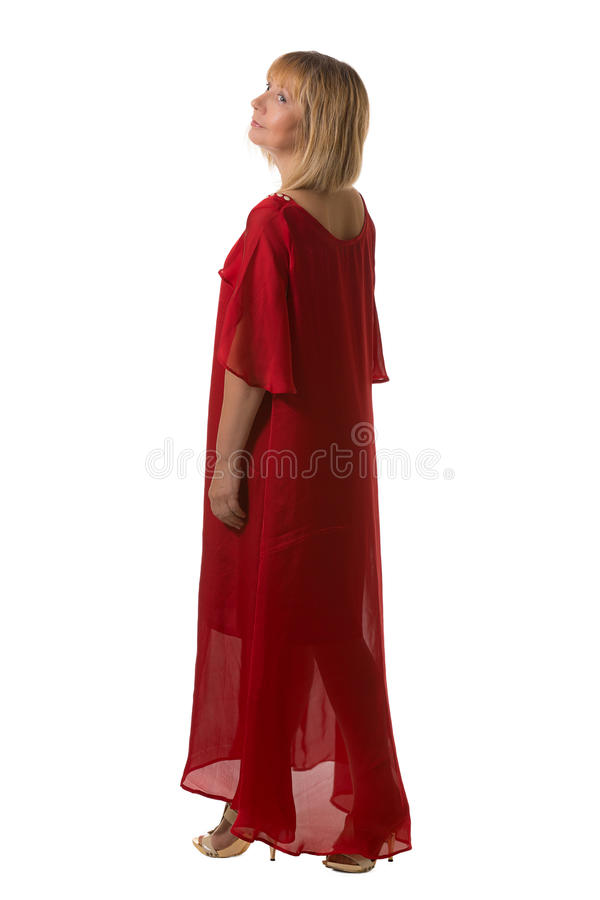 Femme dans la robe rouge d'élégance reculant et regardant le côté images stock