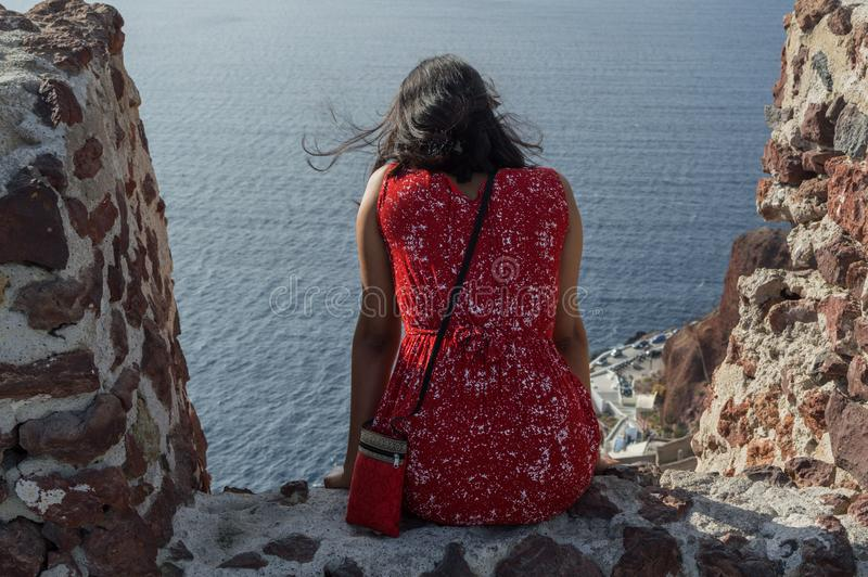 Femme dans la robe rouge regardant la mer à Oia, Santorini, Cyclade photos libres de droits