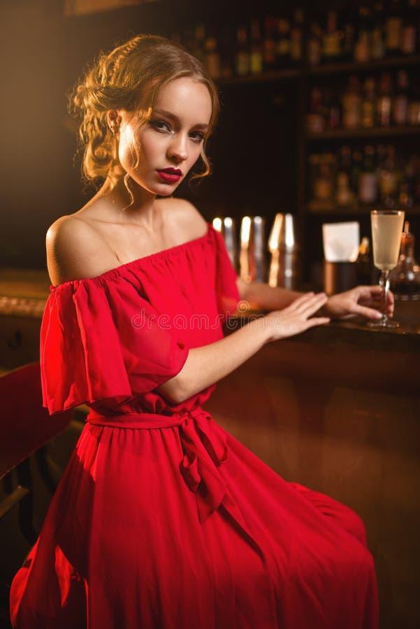Femme dans la robe rouge se tenant au compteur de barre photo libre de droits