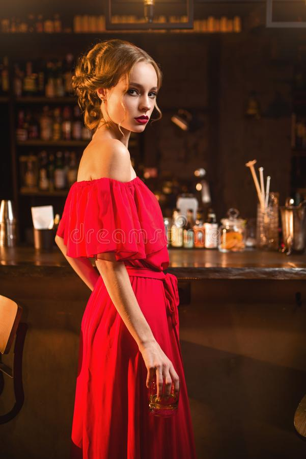 Femme dans la robe rouge se tenant au compteur de barre image stock