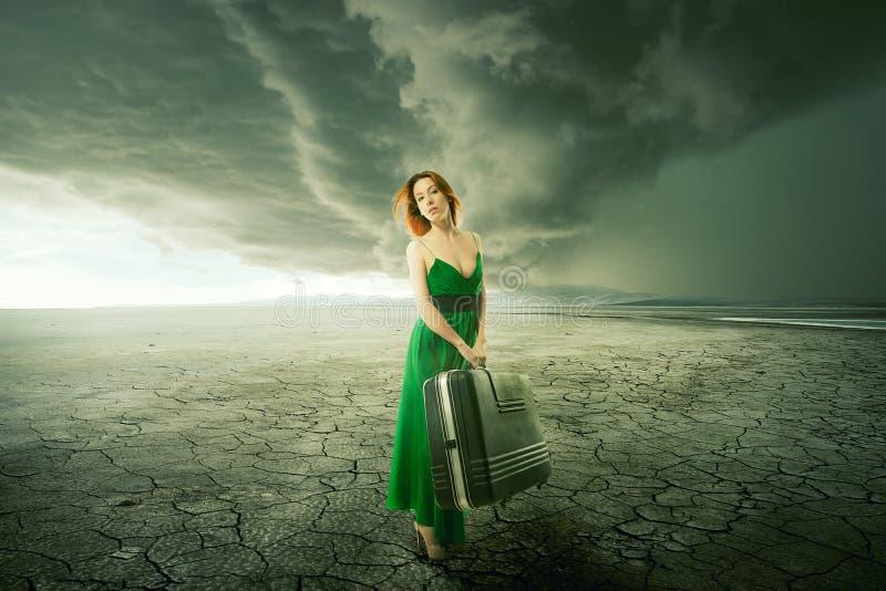 Femme dans la robe verte avec la valise seul se tenant au milieu du désert photographie stock