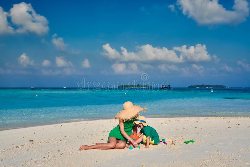 Femme dans la robe verte avec le gar?on trois an sur la plage photos stock