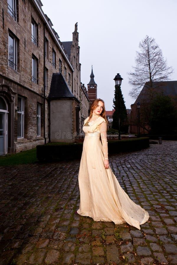 Femme dans la robe victorienne dans une vieille place de ville dans la marche de soirée photos stock