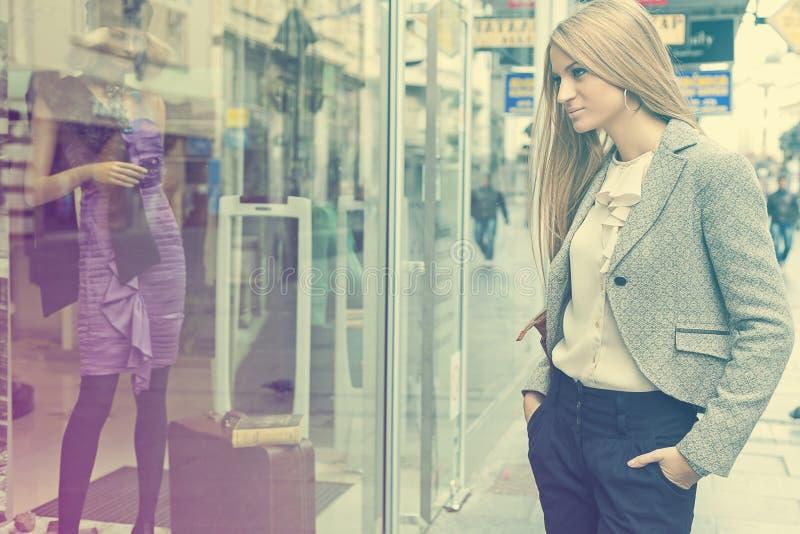 Femme dans la rue shoping regardant l'hublot photographie stock libre de droits