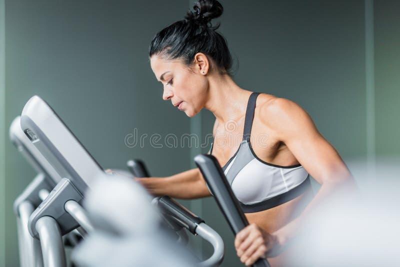 Femme dans la séance d'entraînement épuisante sur l'entraîneur elliptique photos libres de droits