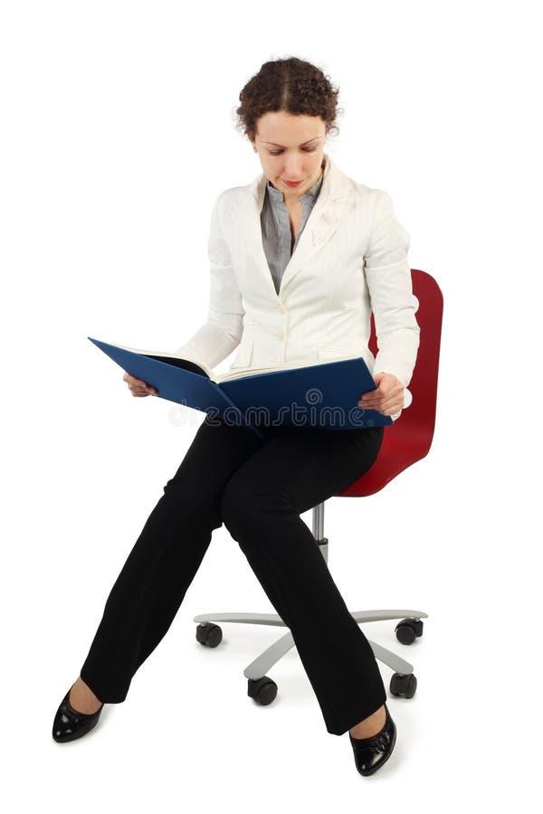 Femme dans la séance de robe d'affaires et affichée images stock