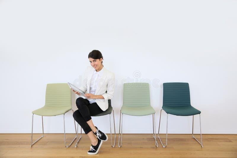 Femme dans la salle d'attente avec le comprimé photographie stock