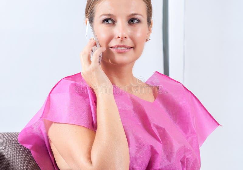 Femme dans la salle d'attente de clinique parlant au sourire de téléphone images stock