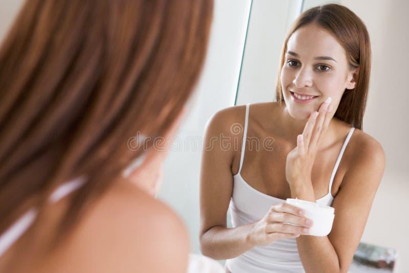Femme dans la salle de bains appliquant la crème de visage image stock