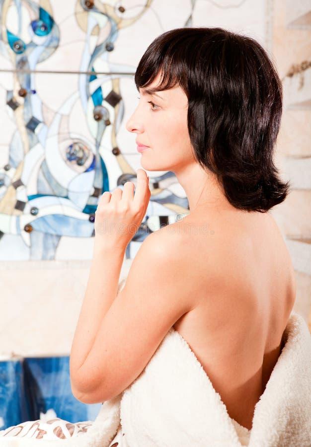 Femme dans la salle de bains enveloppée dans le manteau images stock