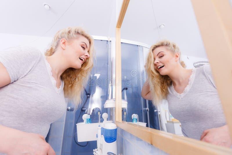 Femme dans la salle de bains regardant le miroir photo stock