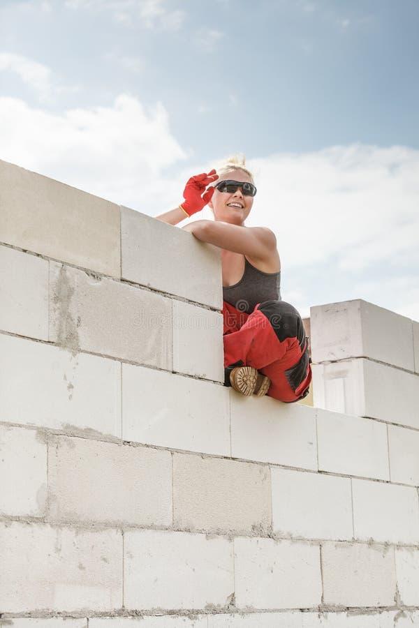 Femme dans la salopette travaillant au chantier de construction images stock