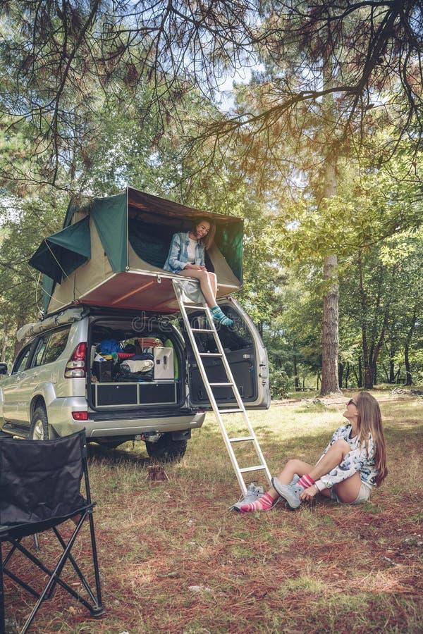 Femme dans la tente au-dessus de la voiture et autre mettant augmentant des bottes image stock