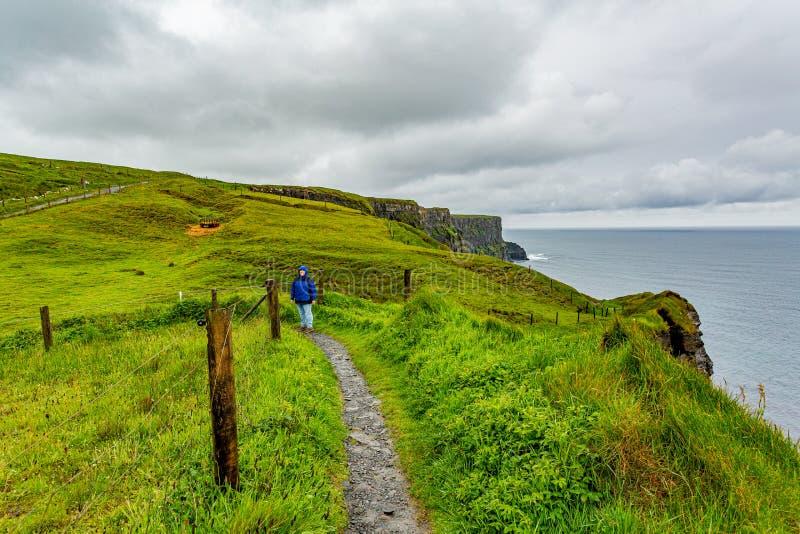 Femme dans la veste bleue appréciant l'itinéraire côtier de promenade de Doolin aux falaises de Moher photo libre de droits