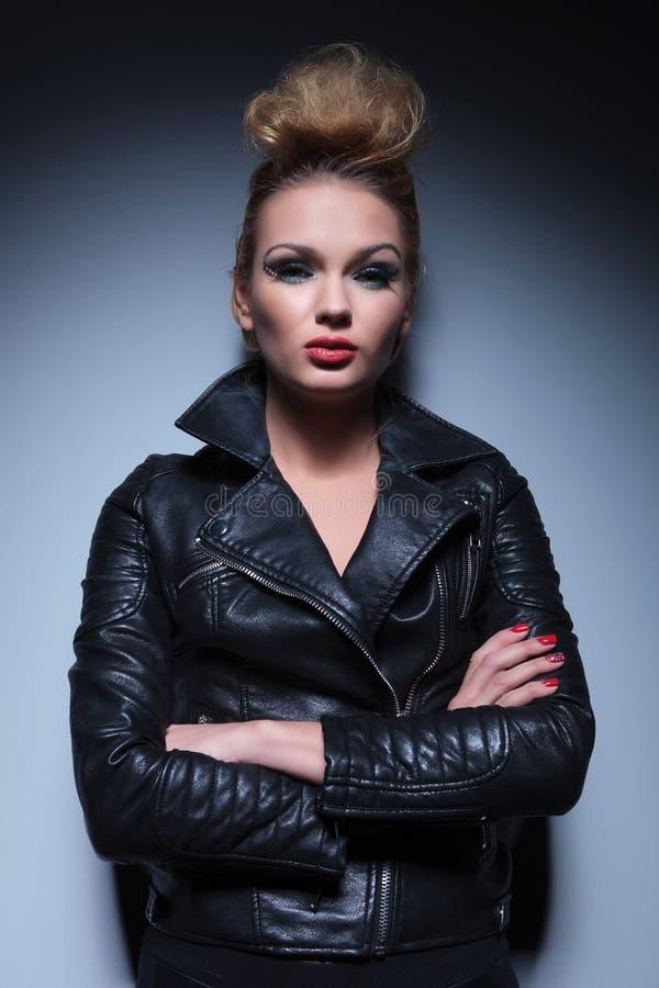 Femme dans la veste en cuir se tenant avec des bras croisés photo libre de droits