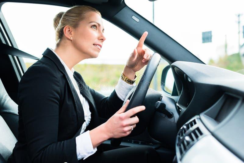 Femme dans la voiture étant fâchée maudissant l'autre conducteur photographie stock