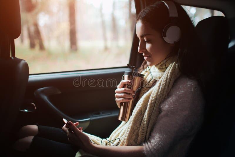 Femme dans la voiture, concept d'automne Jolie fille de sourire écoutant la musique avec des écouteurs et lisant un livre se dépl image libre de droits