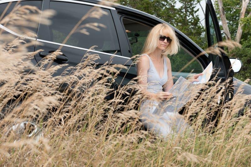 Femme dans la voiture regardant la carte photos libres de droits