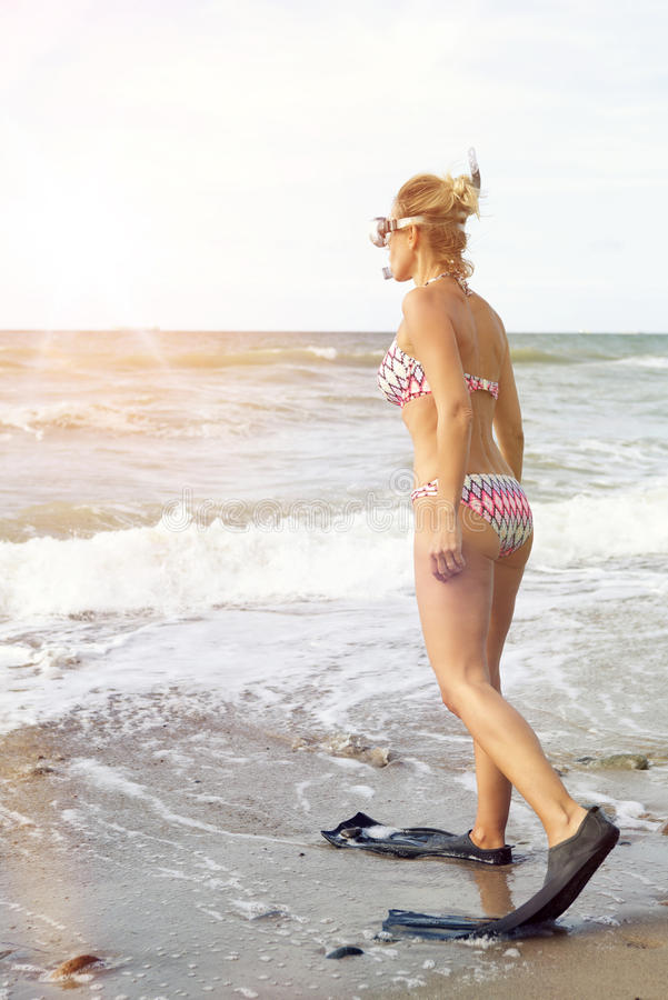 Femme dans le bikini avec des nageoires et des lunettes sur la plage photo stock