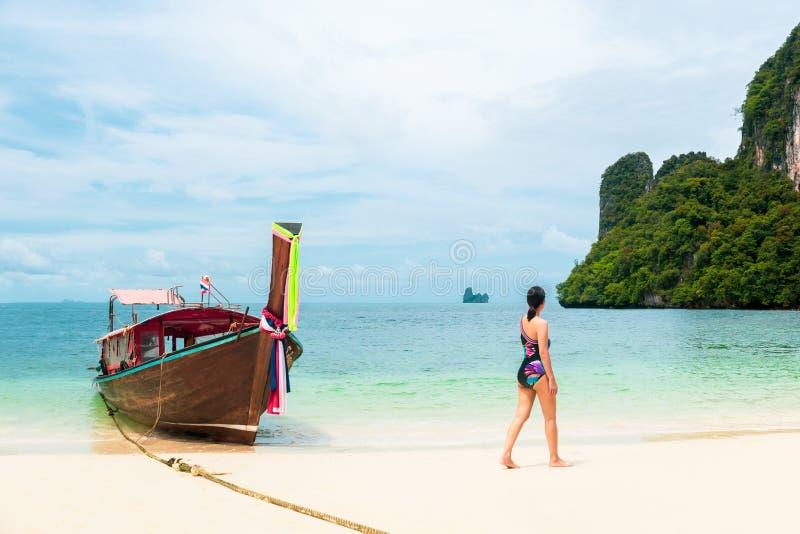 Femme dans le bikini marchant sur la plage avec le bateau de longue queue en île tropicale photos stock