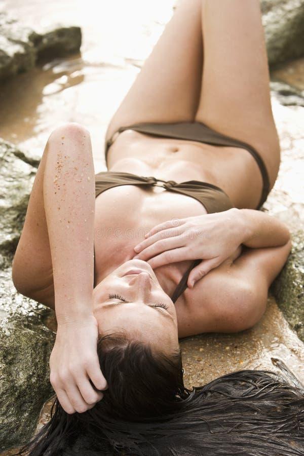 Femme dans le bikini s'étendant sur la plage rocheuse photographie stock