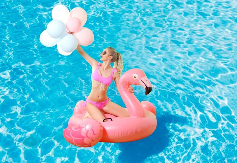 Femme dans le bikini sur le matelas gonflable dans la piscine photos stock