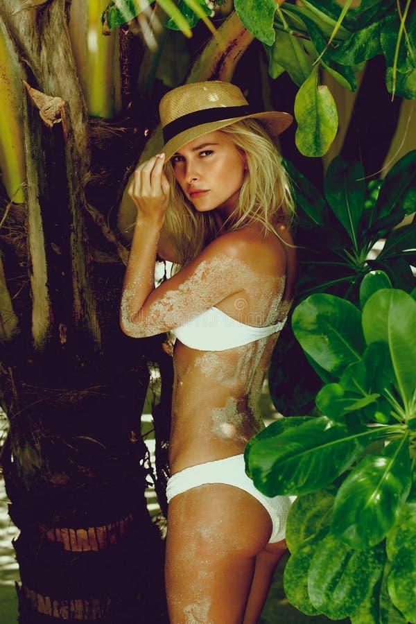 Femme dans le bikini sur une plage tropicale avec des palmiers photographie stock