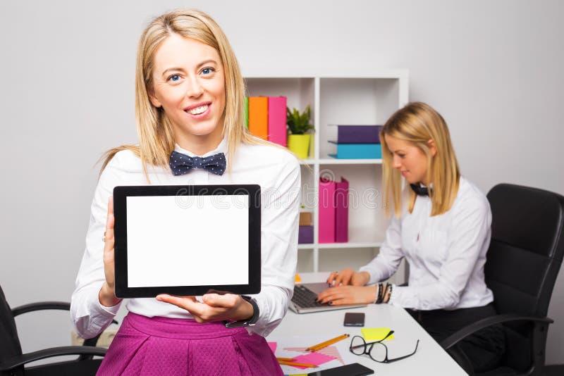 Femme dans le bureau tenant le comprimé photo stock