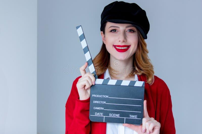Femme dans le cardigan rouge et chapeau avec le bardeau photos stock
