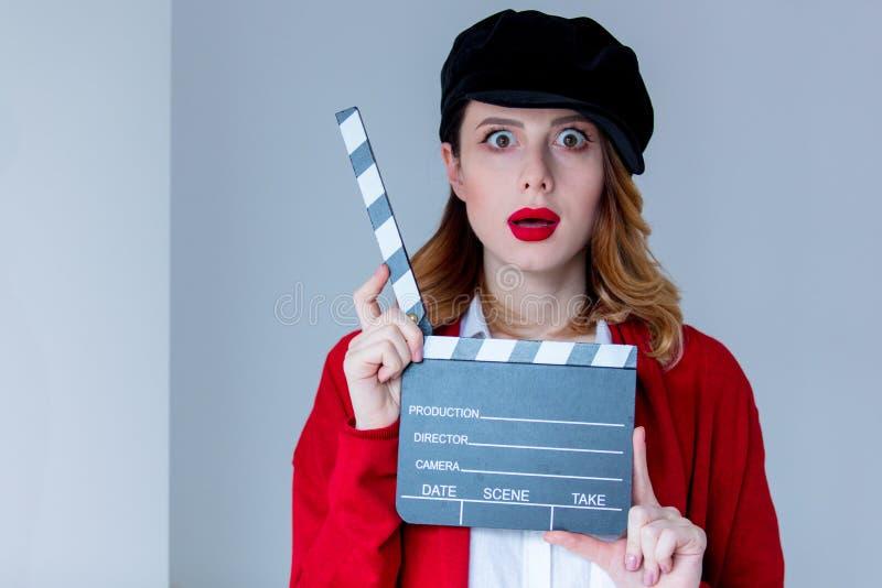 Femme dans le cardigan rouge et chapeau avec le bardeau image stock