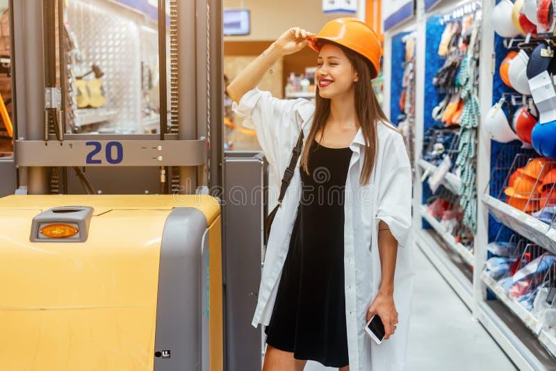 Femme dans le casque orange de construction au fond de tache floue de supermarché image libre de droits