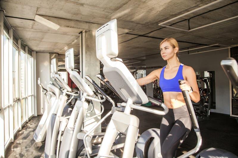Femme dans le centre de fitness ou gymnase, tour sur l'orbitrack photographie stock libre de droits