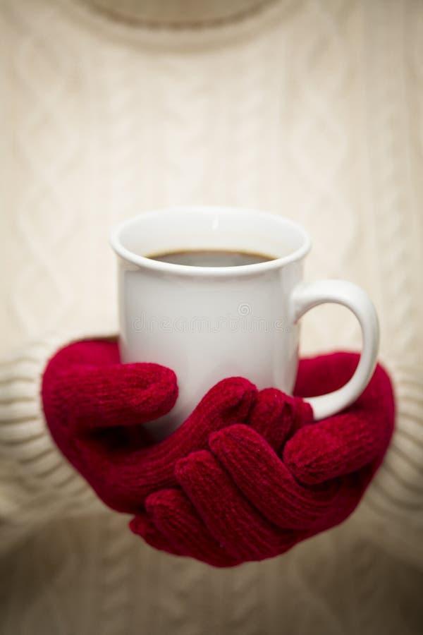Femme dans le chandail avec les mitaines rouges tenant la tasse de café photos libres de droits