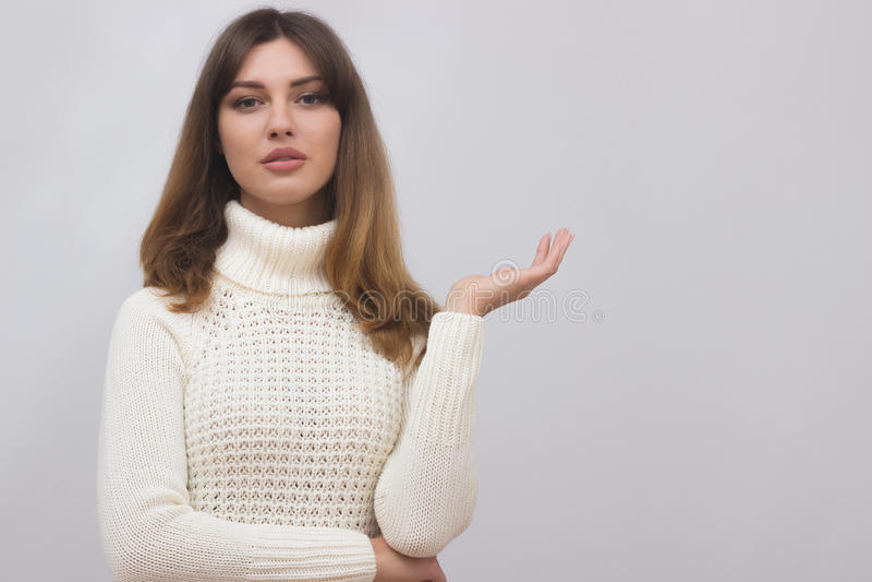 Femme dans le chandail blanc montrant quelque chose avec la paume ouverte de main photos stock