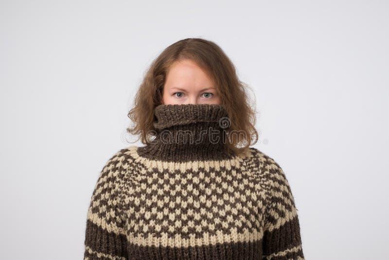 Femme dans le chandail brun chaud cachant son visage Seulement des yeux sont vus Elle veut rester l'anonyme photos stock