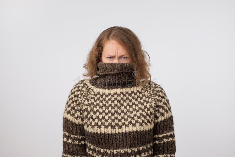 Femme dans le chandail brun chaud cachant son visage Seulement des yeux sont vus Elle veut rester l'anonyme images stock