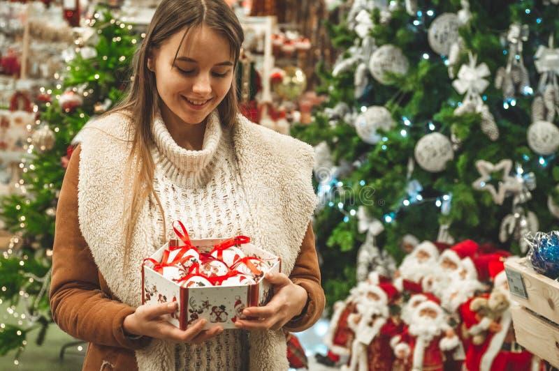 Femme dans le chandail de laine chaud blanc tenant les boules décoratives en verre d'un jouet de boîte dans des mains, l'espace d photo libre de droits