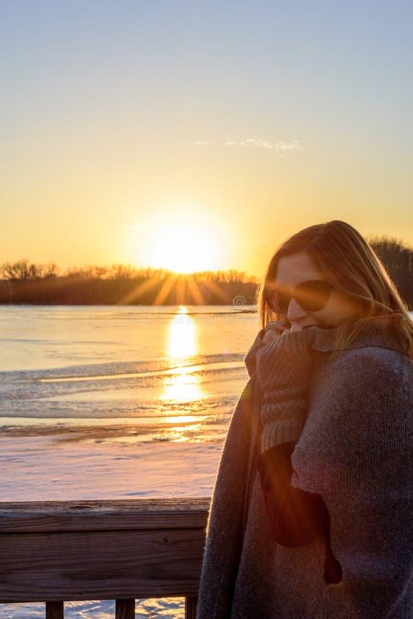 Femme dans le chandail se tenant sur le pont à côté du lac congelé au coucher du soleil photographie stock libre de droits