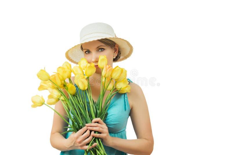 Femme dans le chapeau d'été avec un bouquet des tulipes d'isolement sur le fond blanc photographie stock