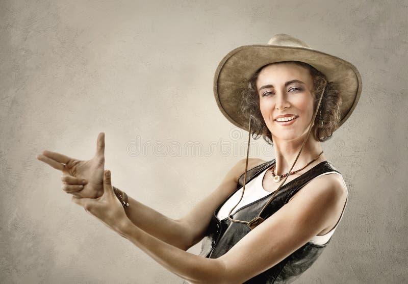 Femme dans le chapeau de cowboy, faisant le geste avec des mains feignant l'arme à feu photo stock