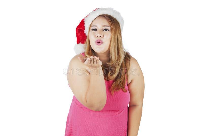 Femme dans le chapeau de Noël soufflant un baiser image stock