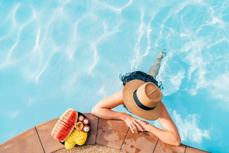 Femme dans le chapeau de paille et le bikini dans des lunettes de soleil à la piscine appréciant les fruits tropicaux frais images stock