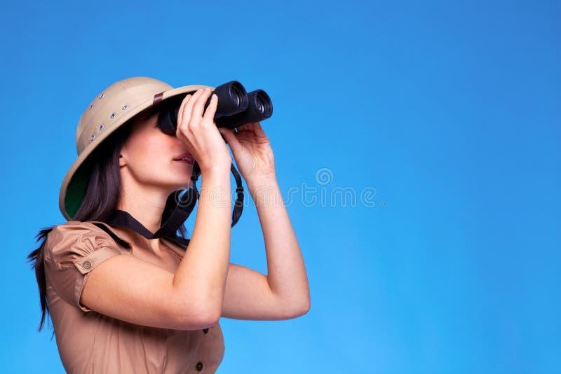 Femme dans le chapeau de safari recherchant avec des jumelles photos stock