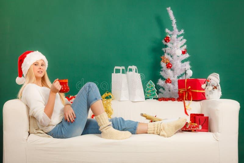Femme dans le chapeau de Santa buvant de la tasse photo libre de droits