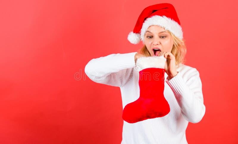 Femme dans le chapeau de Santa déballant le fond de rouge de cadeau de Noël Vérifiez le contenu du bas de Noël ce qu'elle a reçu images stock