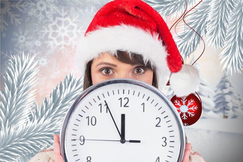 Femme dans le chapeau de Santa se cachant derrière une horloge images libres de droits