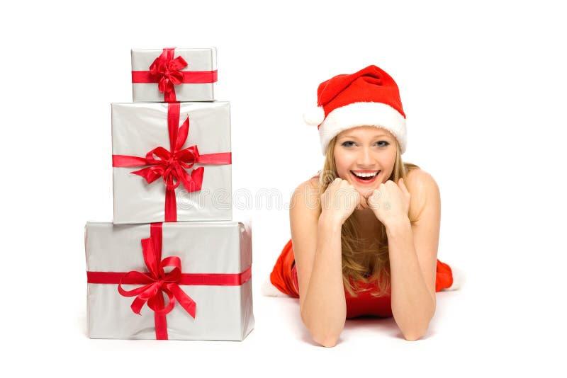 Femme dans le chapeau de Santa se couchant avec des cadeaux photo stock
