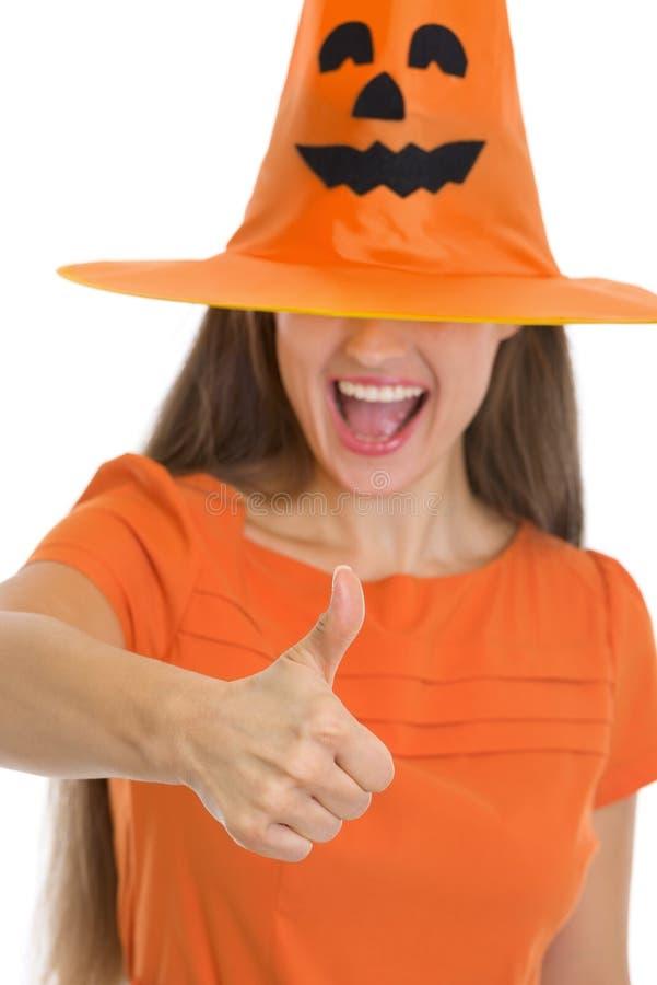 Femme dans le chapeau de Veille de la toussaint au-dessus des yeux affichant des pouces vers le haut photo stock