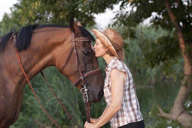 Femme dans le chapeau embrassant le cheval. photographie stock
